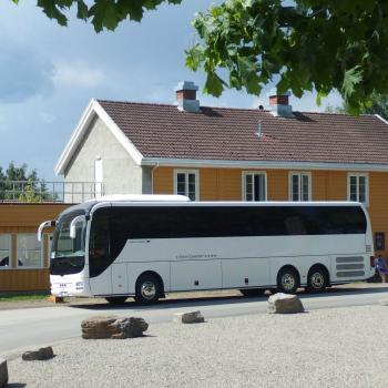 Hvit buss på tur, parkert foran to hus