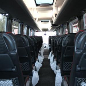 Buss innvendig, fra baksetet og framover i midtgangen.