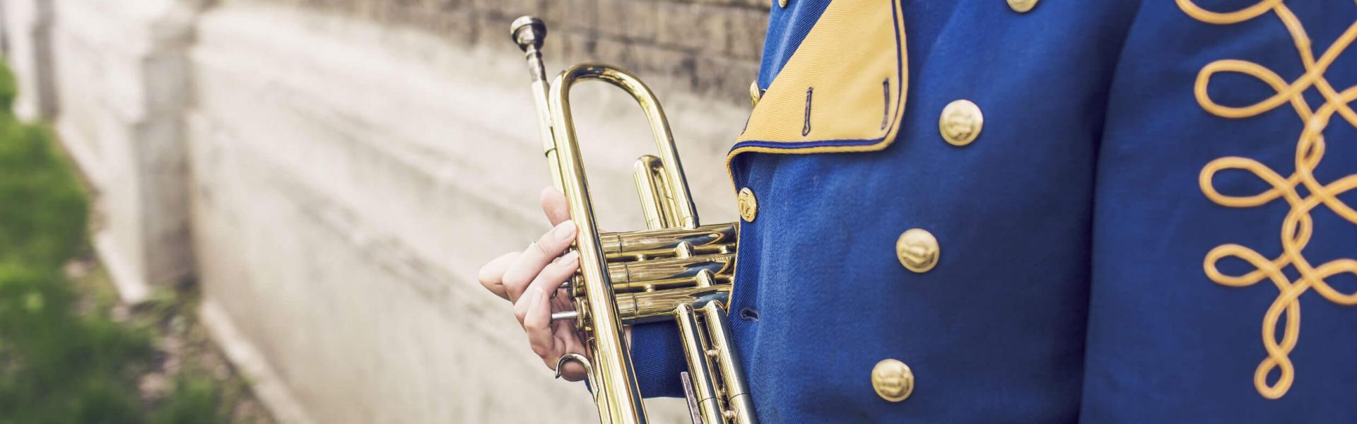 Musikant som spiller i korps med trompet og uniform