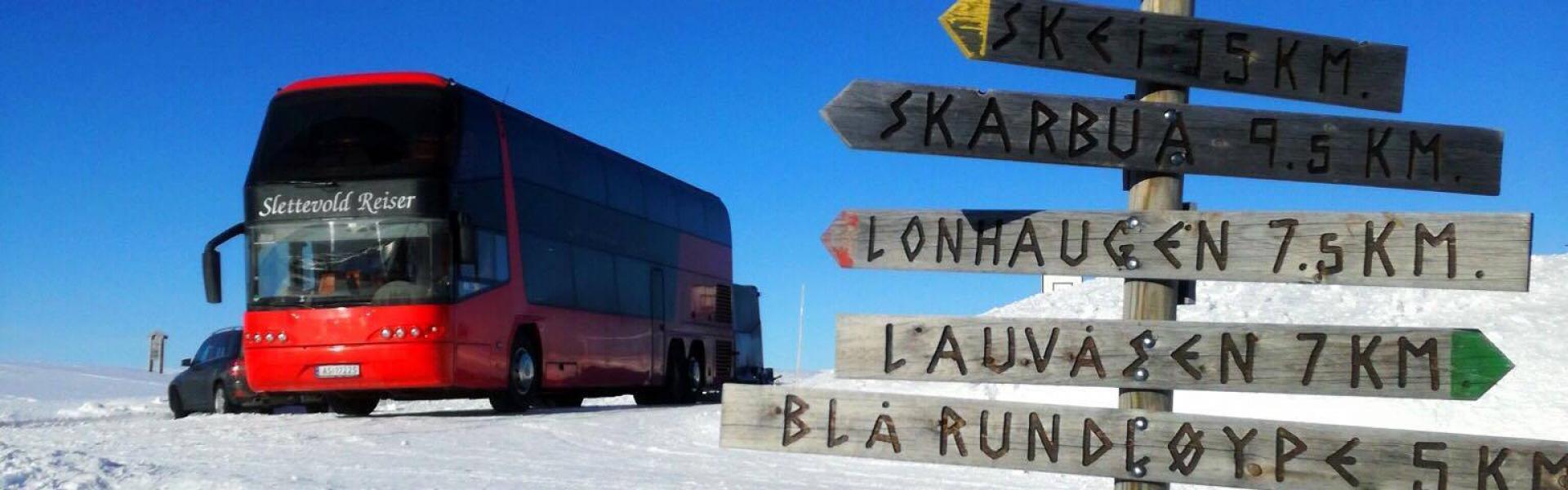 Turbuss på fjelltur. Dobbeltdekker rød buss parkert på snøen i fint vær - Gålå - Gausdal - Ringebu