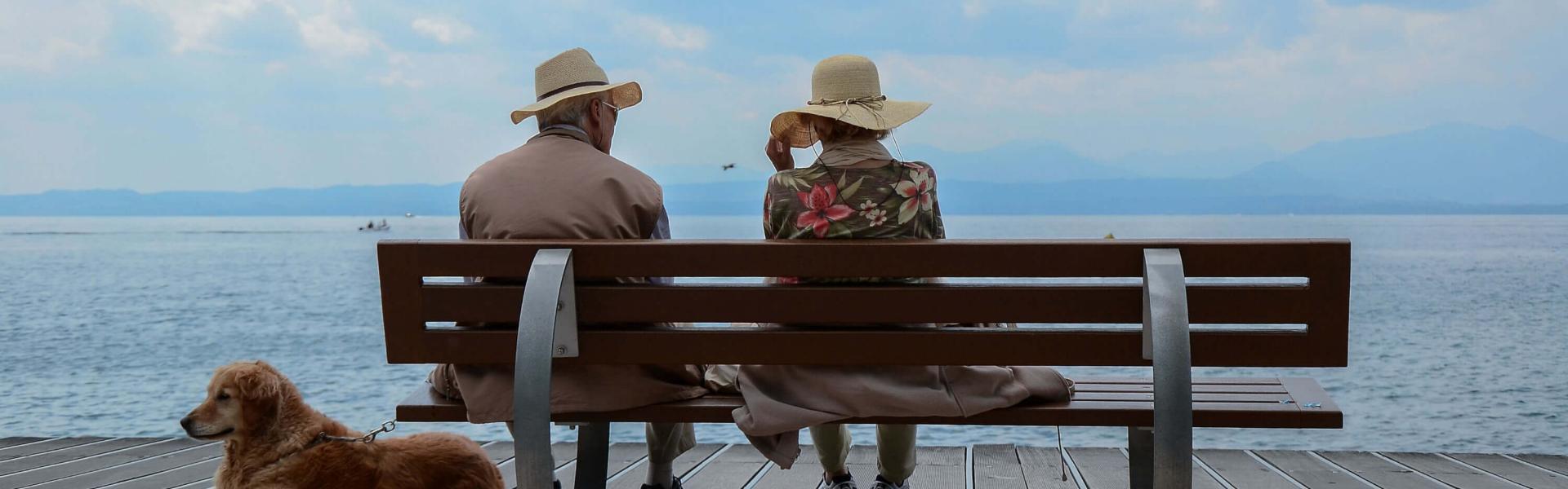 To pensjonister på tur sittende på benk med utsikt ut over havet